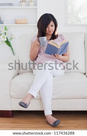 Woman reading a book while holding a mug on a sofa - stock photo