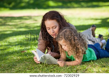 Woman reading a book with her daughter - stock photo