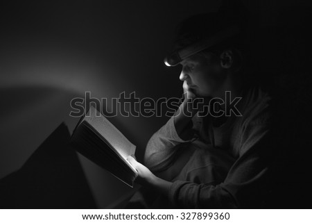 Woman reading a book with the torch while electricity is off
