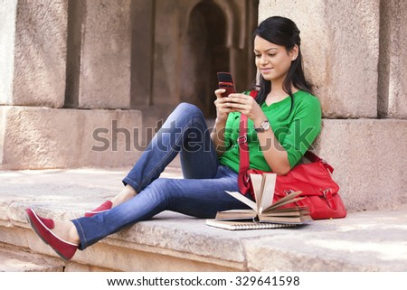 Woman reading an sms on a mobile phone - stock photo