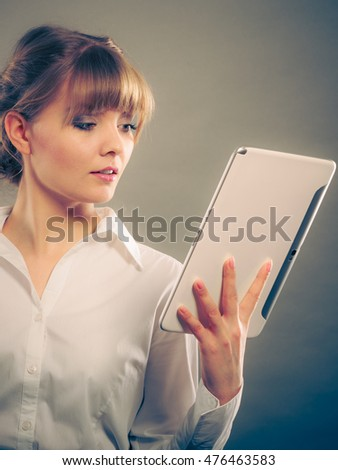 Woman reading and learning with ebook digital tablet. Education leisure. Young girl in white shirt studying for exam. Instagram filtered.