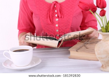 Woman reading book and  drink coffee, close-up - stock photo