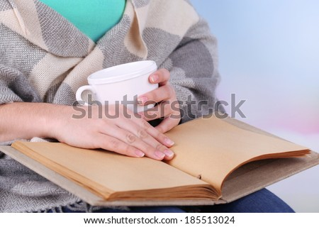 Woman reading book and  drink coffee or tea, close-up - stock photo