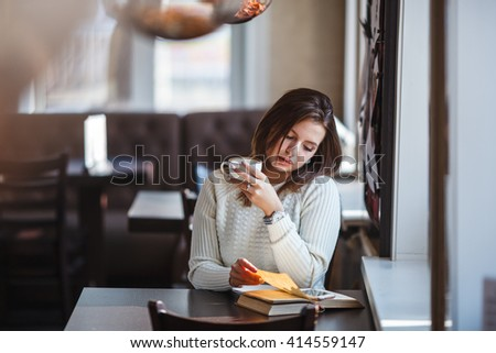 woman reading book at cafe near window