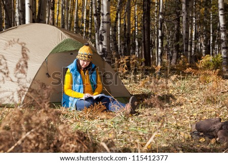 Woman Reading Book at Campsite