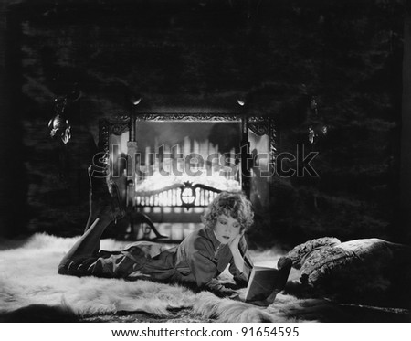 Woman reading book by the fire - stock photo