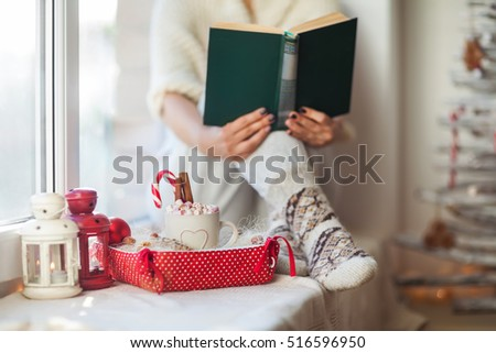 Woman reading book in christmas decorated home. Holiday concept