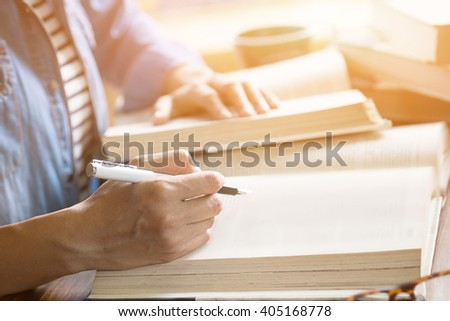 Woman reading book in library or cafe. - stock photo