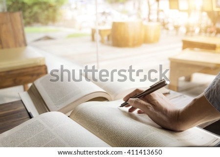 Woman reading book in library. Retro filter effect,soft focus,low light.(selective focus) - stock photo