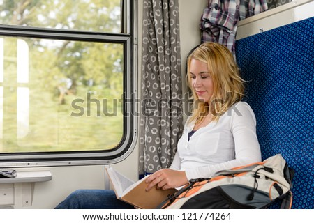 Woman reading book in train smiling commuter leisure journey vacation - stock photo