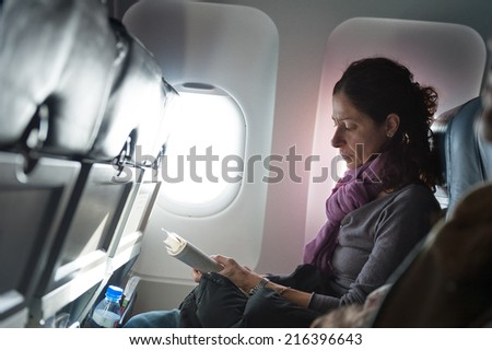 Woman reading book inside airplane.