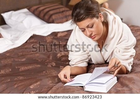 Woman reading book on bedroom - stock photo