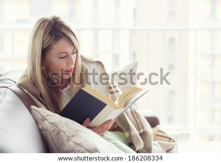 Woman reading book on couch - stock photo
