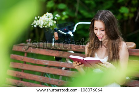 Woman reading book on park bench - stock photo