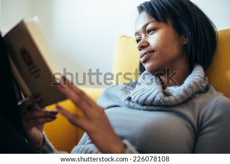 Woman reading book on the couch - stock photo