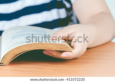 Woman reading book on the table - stock photo