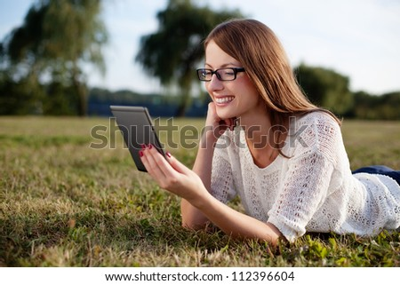 Woman reading e-book in nature. - stock photo