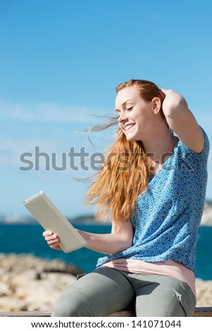 Woman reading her tablet in a sea breeze at the coast while trying to hold back her hair with her hand - stock photo