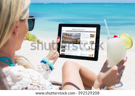 Woman reading news on tablet while relaxing on the beach. Contents are all made up. - stock photo