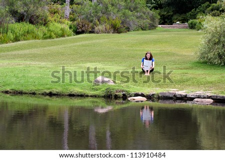 Woman reading newspaper sitting in grass with a pond in the foreground - stock photo