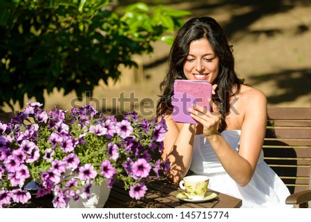 Woman reading novel on ebook and enjoying morning breakfast on summer in garden. Female reader and electronic book. - stock photo