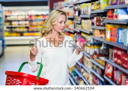 Woman reading nutritional values at supermarket - stock photo