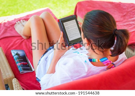 Woman reading on electronic book on summer holidays - stock photo