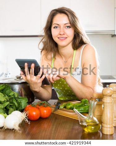 Woman reading recipes with a tablet in hands in the kitchen - stock photo