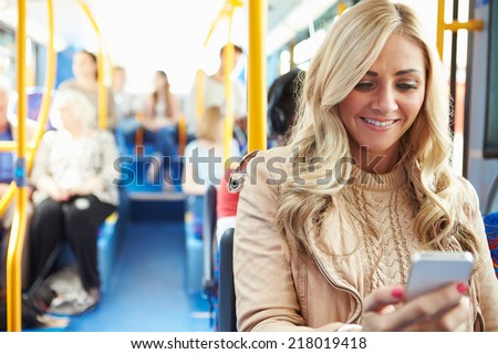 Woman Reading Text Message On Bus - stock photo
