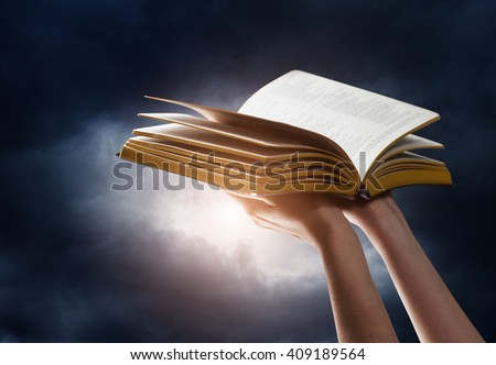 woman reading the bible in the darkness - stock photo