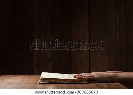 woman reading the bible in the darkness over wooden table - stock photo