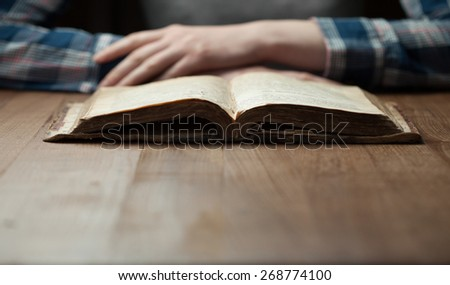 woman reading the bible in the darkness over wooden table. Bible is opened on a table - stock photo
