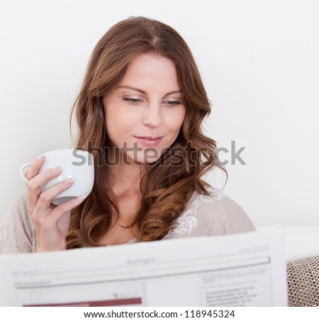 Woman reading the newspaper while drinking a refreshing cup of morning coffee - stock photo
