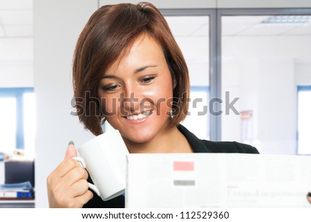 Woman reading the newspaper while drinking coffee - stock photo