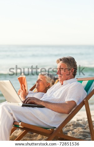 Woman reading while her husband is working on his laptop