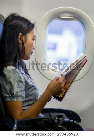 Woman reads a journal  in a plane next to a window. Entertainment on the aircraft. The passenger on the airplane reading a magazine. - stock photo