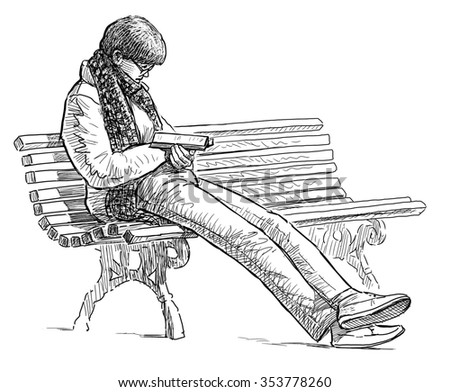 woman reads on the park bench