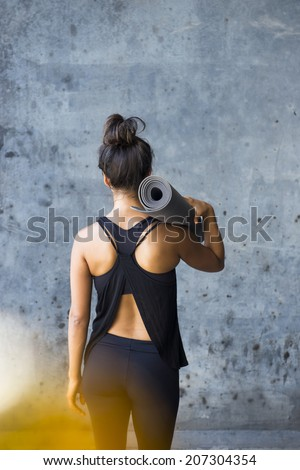 Woman ready to practice yoga in a urban enviromment - stock photo