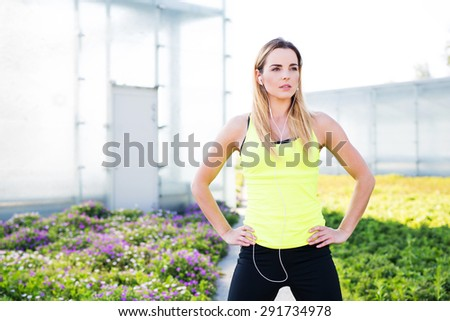 Woman ready to run looking into a distance with earphones on - stock photo