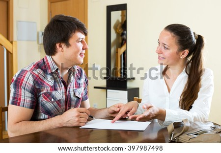 woman real estate agent signing agreement at home - stock photo