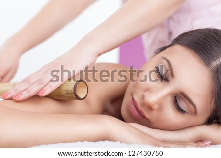 Woman receives bamboo massage at spa salon