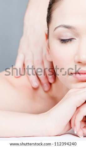 Woman receives body massage at spa salon. Half face