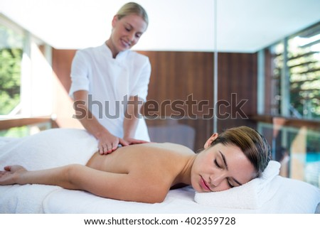 Woman receiving a back massage at spa - stock photo