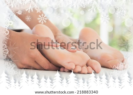 Woman receiving a foot massage against fir tree forest and snowflakes - stock photo