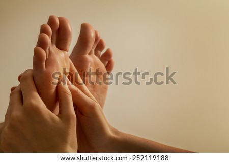 Woman receiving a foot massage at the health spa center - stock photo