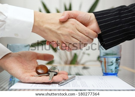 woman receiving a handshake and a house key at the same time - stock photo