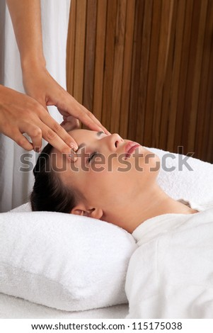 Woman receiving a head massage in spa. - stock photo