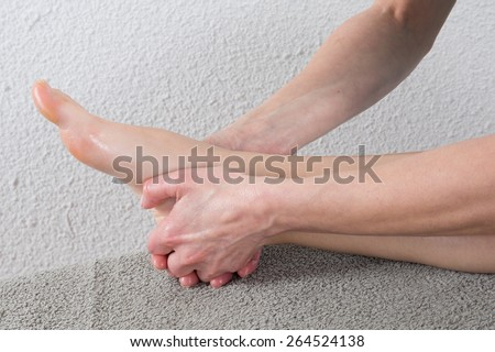woman receiving a massage on  her painful ankle