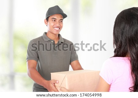 Woman receiving a package at home from a delivery guy - stock photo