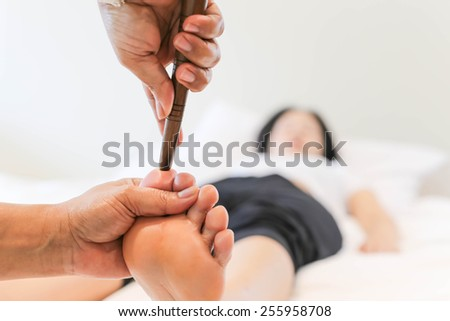 Woman receiving a Reflexology foot massage in spa - stock photo